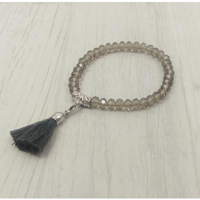 Bracelet gris clair en perles de verre et pompon